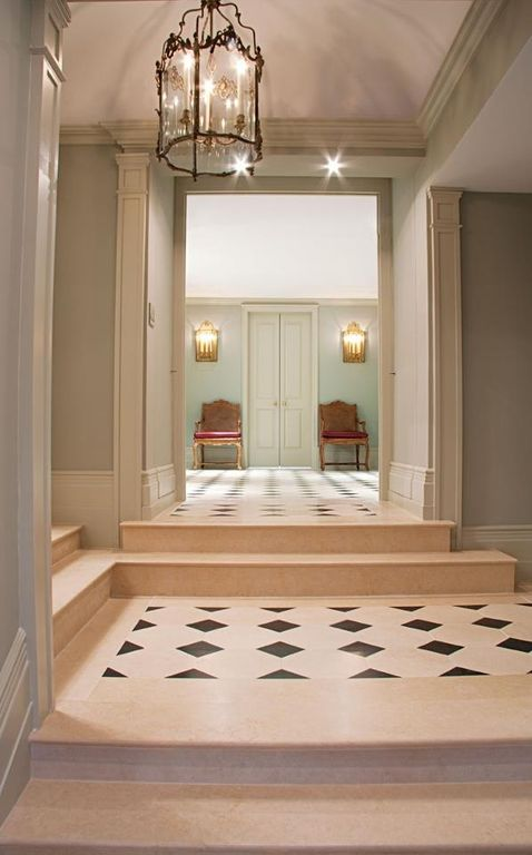 Traditional Hallway with High ceiling, French doors, can lights, Crown molding, stone tile floors, Chandelier, Wall sconce