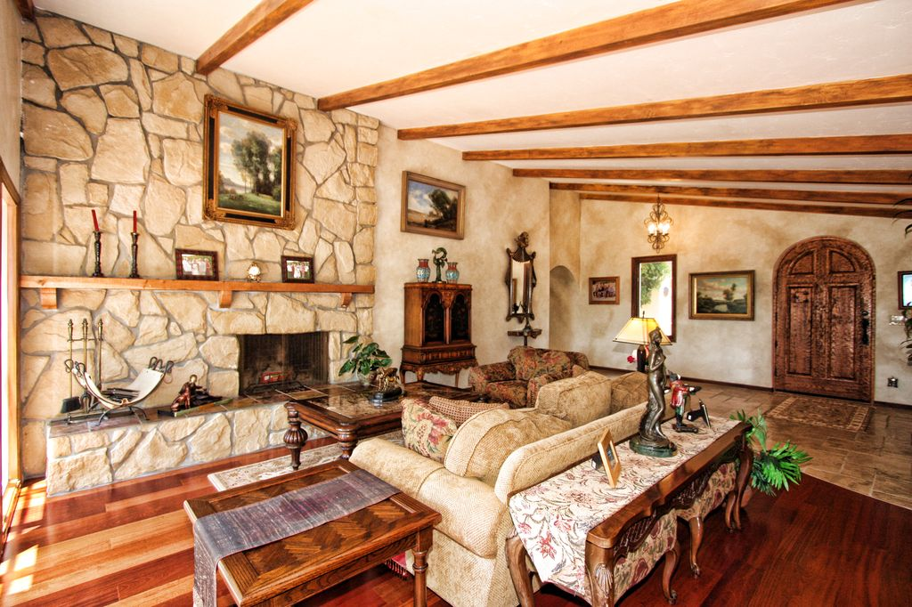 Mediterranean Living Room with Hardwood floors, Exposed beam, Fireplace, Standard height, stone fireplace