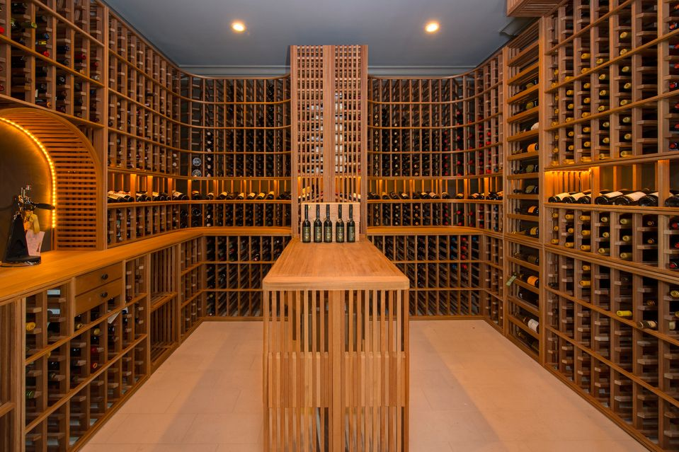 Craftsman Wine Cellar with stone tile floors, Crown molding, Built-in bookshelf, can lights, Standard height