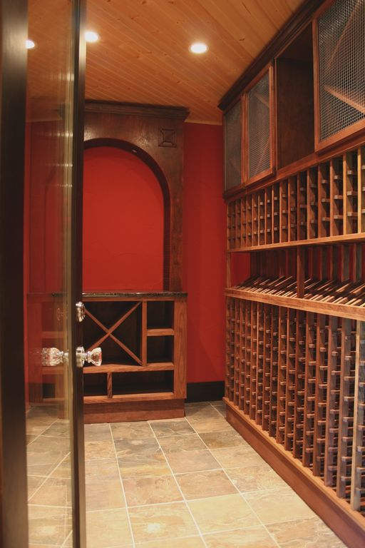 Craftsman Wine Cellar with French doors, Standard height, stone tile floors, can lights, onyx tile floors, Crown molding