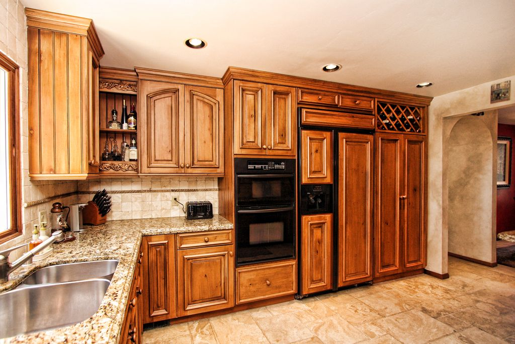 Traditional Kitchen with Raised panel, Framed Partial Panel, L-shaped, Simple granite counters, Multiple Sinks, Stone Tile