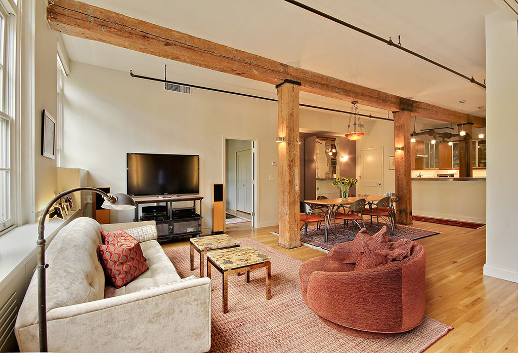 Modern Living Room with Built-in bookshelf, double-hung window, Wall sconce, Exposed beam, Standard height, Hardwood floors