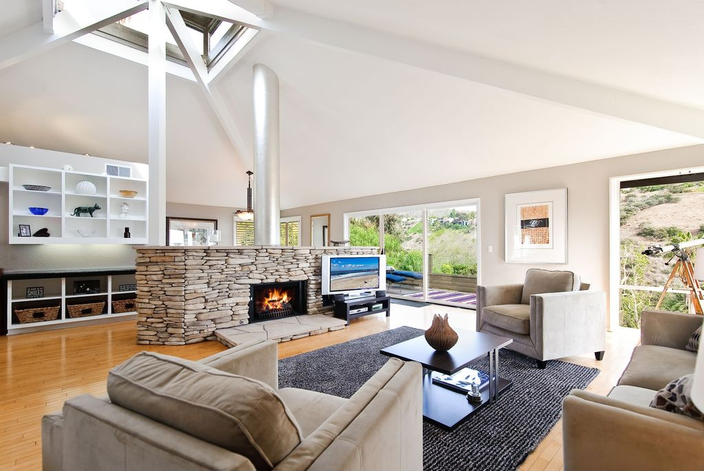 Contemporary Living Room with Built-in bookshelf, Fireplace, picture window, Hardwood floors, Standard height, Skylight