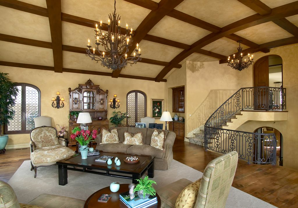 Mediterranean Living Room with Built-in bookshelf, Chandelier, Arched window, Cathedral ceiling, Exposed beam, Wall sconce