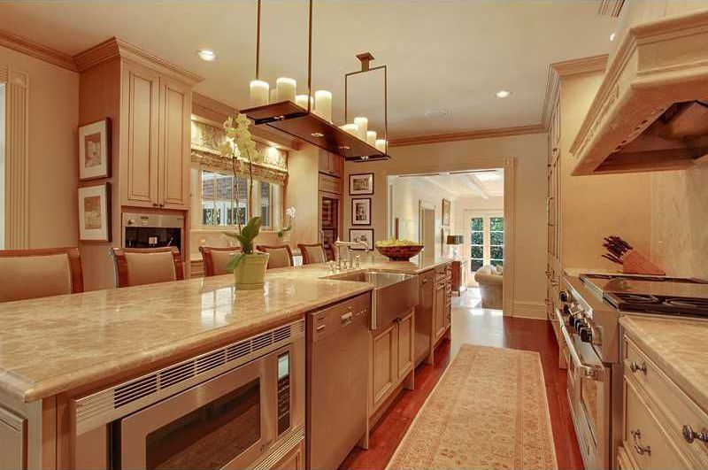 Traditional Kitchen with Laminate floors, Crown molding, Flush, U-shaped, Custom hood, Flat panel cabinets, Farmhouse sink