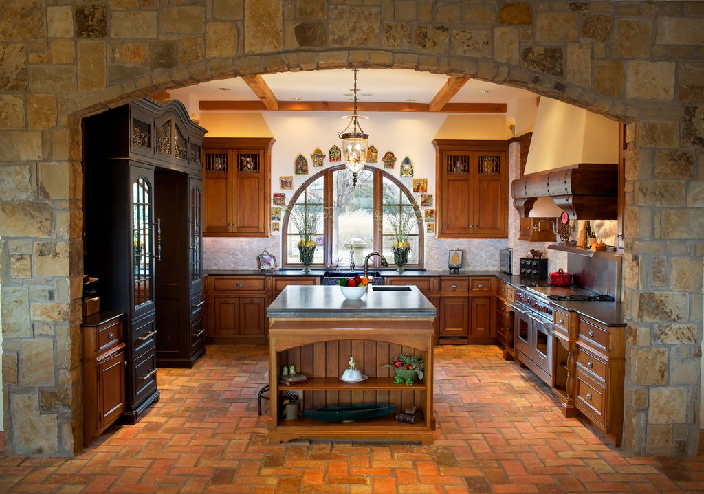 Country Kitchen with Concrete counters, can lights, Framed Partial Panel, Arched window, Pendant light, Custom hood, U-shaped
