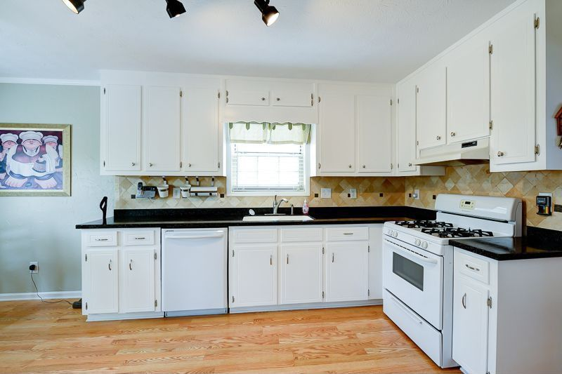 Traditional Kitchen with full backsplash, Soapstone counters, double-hung window, gas range, drop-in sink, flush light