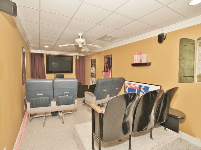Traditional Home Theater with can lights, Carpet, Standard height, Crown molding, Ceiling fan