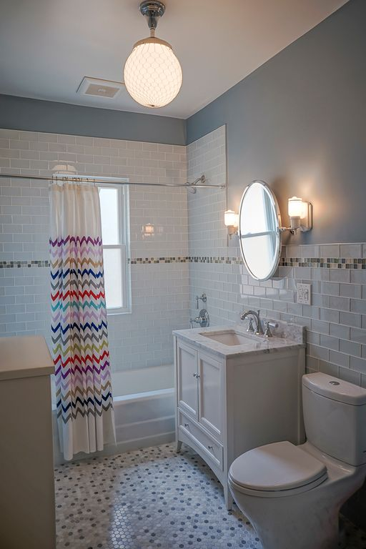 Traditional Full Bathroom with Complex marble counters, tiled wall showerbath, penny tile floors, Flush, flush light