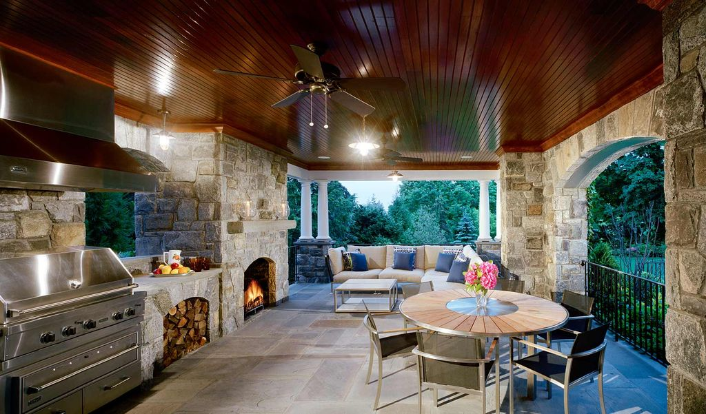 Rustic Porch with outdoor pizza oven, exterior stone floors, Outdoor kitchen, Deck Railing