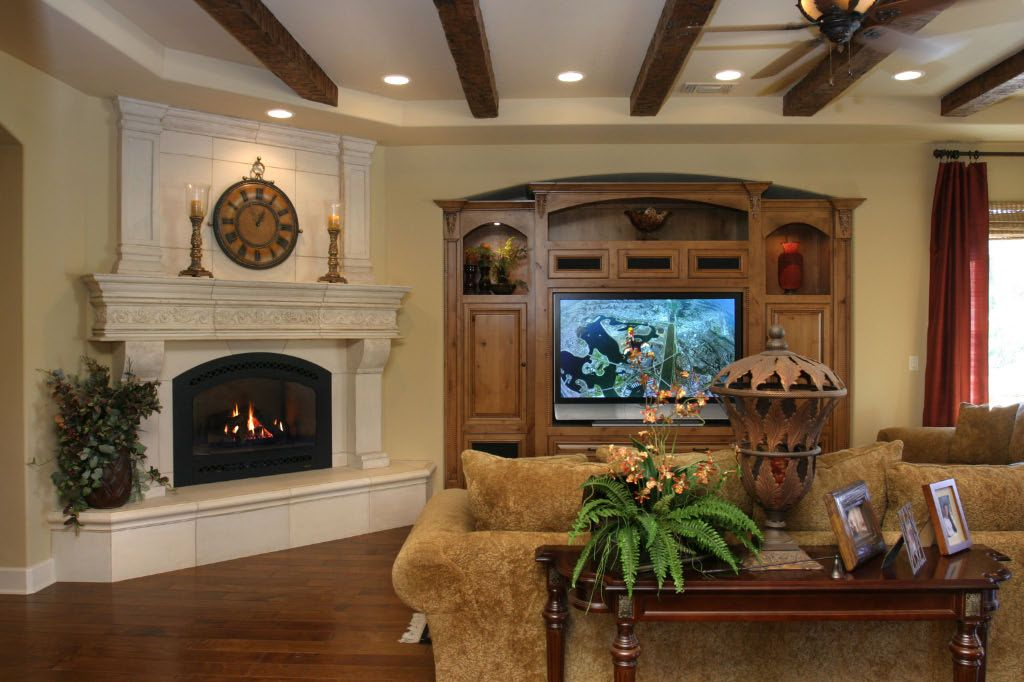 Mediterranean Living Room with Hardwood floors, Cement fireplace, can lights, Exposed beam, Fireplace, Built-in bookshelf