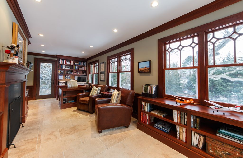 Craftsman Home Office with Built-in bookshelf, limestone tile floors, stone tile floors, French doors, metal fireplace