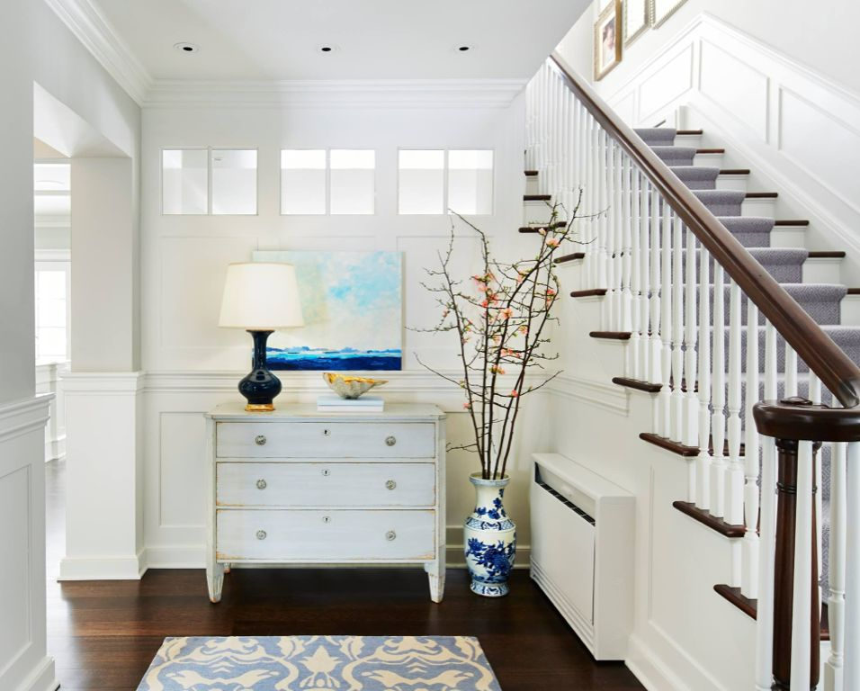 Cottage Entryway with Wainscoting, White wash chest of drawers, Classic ceramic bottle table lamp, Hardwood floors