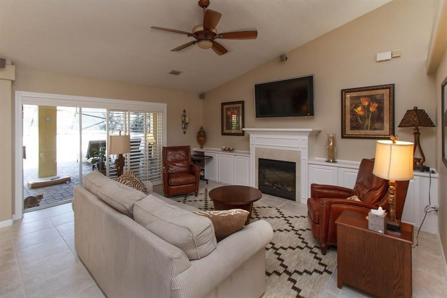 Traditional Living Room with stone tile floors, Fireplace, Ceiling fan, Standard height, sandstone tile floors