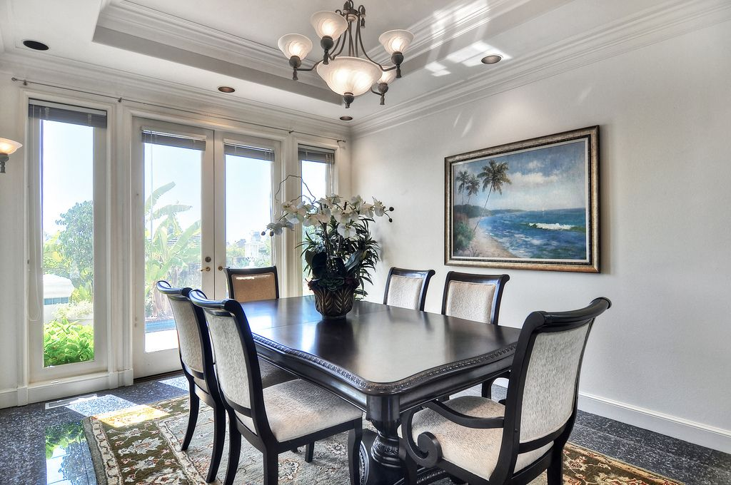 Tropical Dining Room with Standard height, simple granite floors, picture window, Crown molding, Wall sconce, French doors