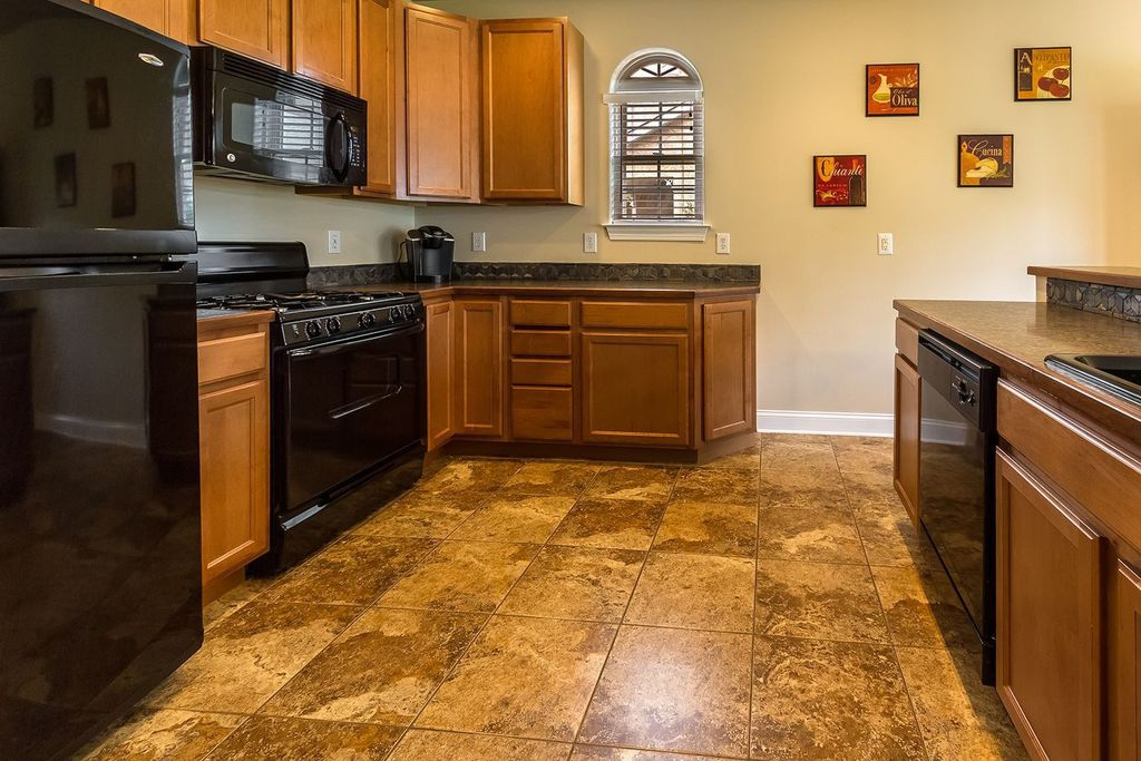 Craftsman Kitchen with Freestanding Full Size Top Freezer Refrigerator, Arched window, Complex granite counters, Slate Tile