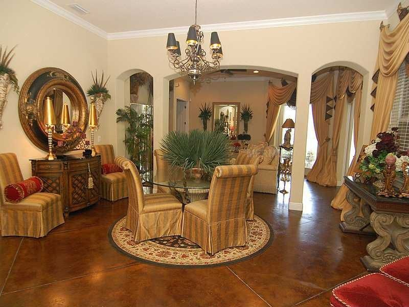 Mediterranean Dining Room with Chandelier, Crown molding, Standard height, Concrete tile , Columns