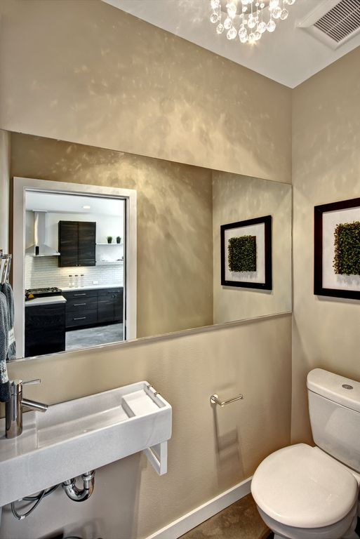 Modern Powder Room with High ceiling, Toto CST416M# Aquia Dual Flush Toilet, Custom Cut Mirror, Concrete floors, Powder room