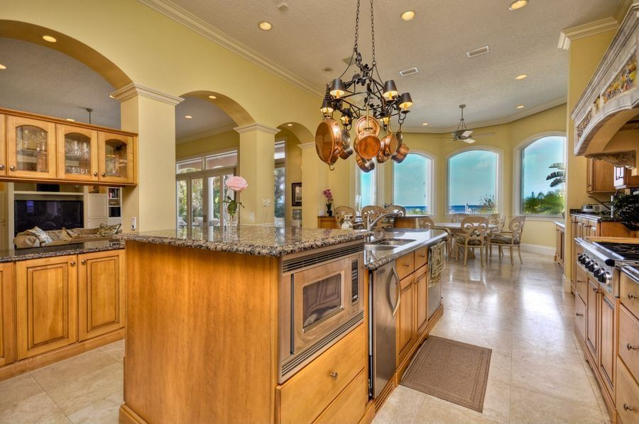 Traditional Kitchen with Framed Partial Panel, Arched window, built-in microwave, can lights, electric cooktop, Glass panel