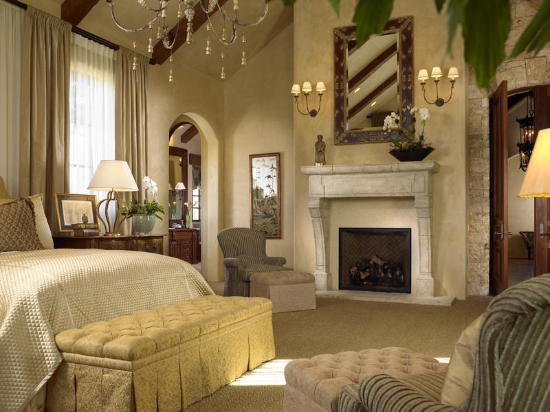 Traditional Master Bedroom with specialty door, Cement fireplace, Fireplace, Chandelier, Casement, Carpet, Exposed beam