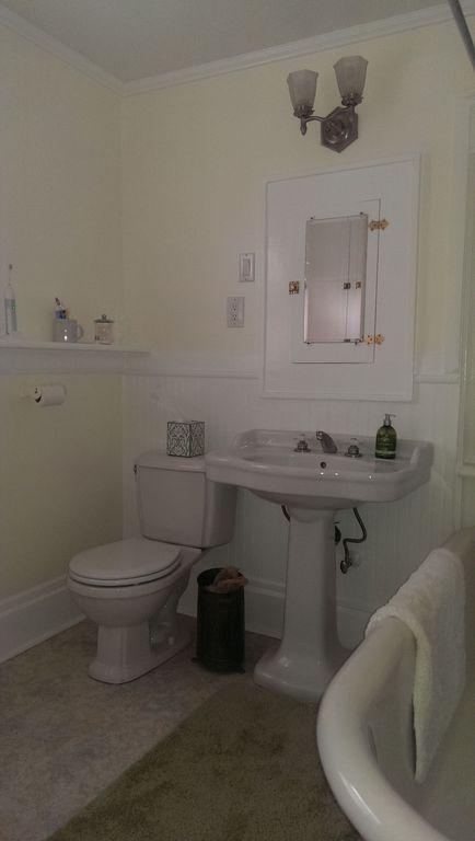 Cottage Full Bathroom with Glass panel, Flush, Pedestal sink, Wainscotting, Bathtub, wall-mounted above mirror bathroom light