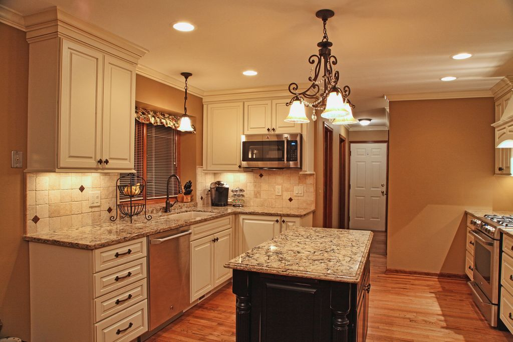 Traditional Kitchen with Crown molding, can lights, Limestone Tile, Kitchen island, gas range, Paint 1, Standard height