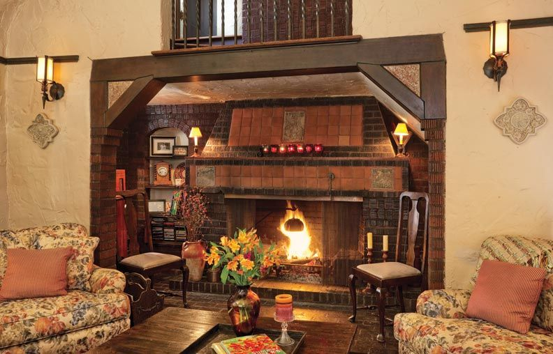 Mediterranean Living Room with High ceiling, Hardwood floors, Wall sconce, Balcony, Fireplace, brick fireplace