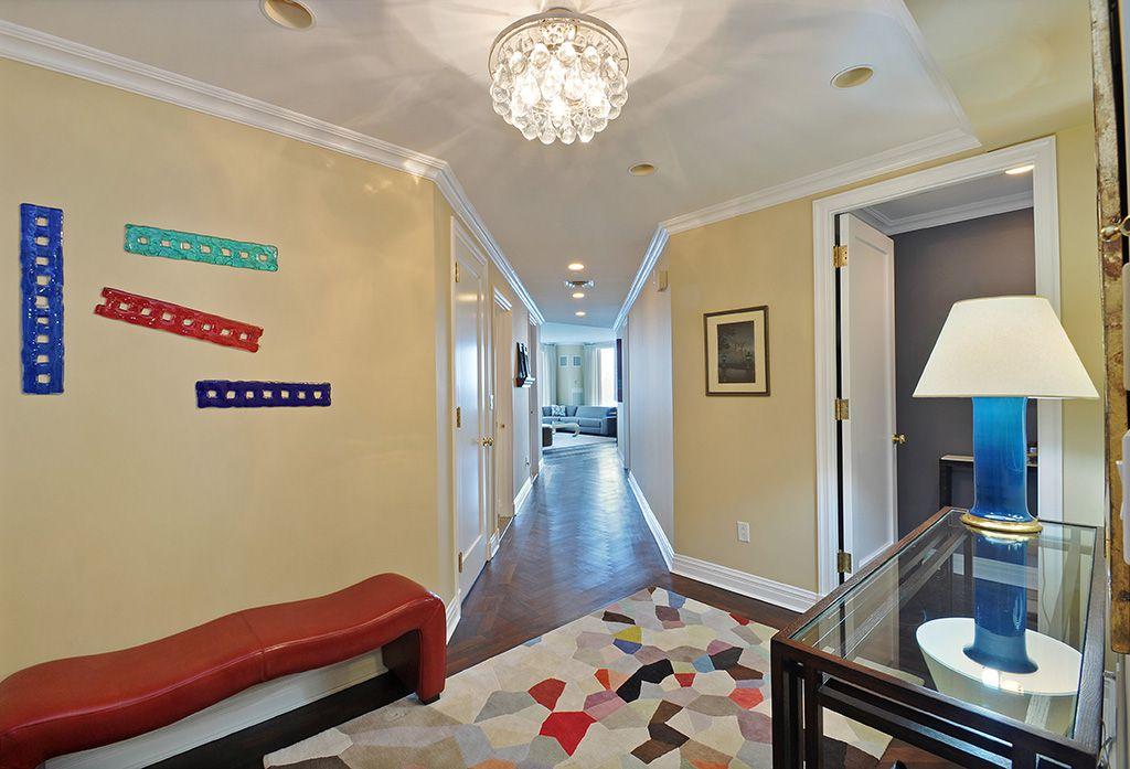Modern Entryway with can lights, flat door, Hardwood floors, Chandelier, Standard height, Crown molding