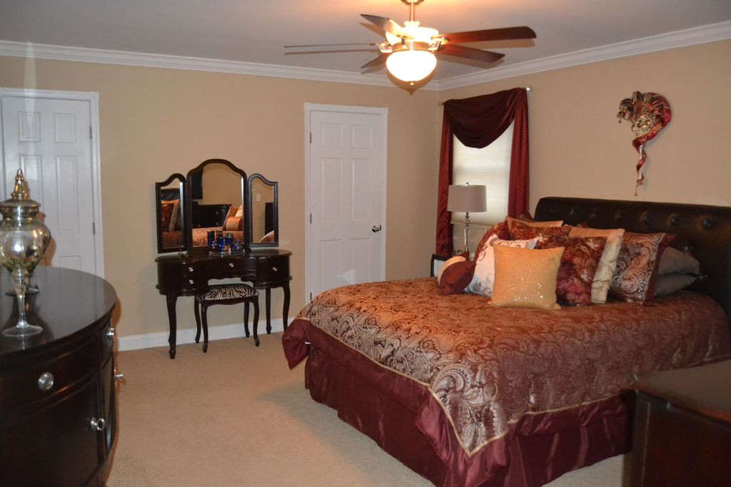 Traditional Master Bedroom with six panel door, Standard height, Carpet, Ceiling fan, Crown molding