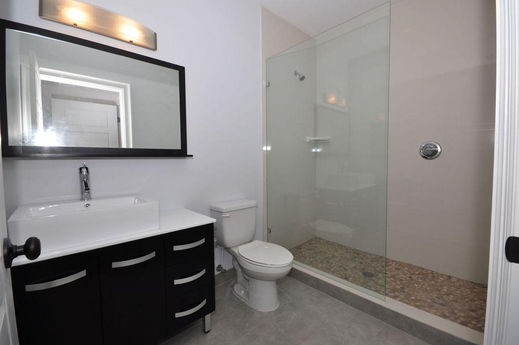 Contemporary 3/4 Bathroom with Vessel sink, limestone tile floors, European Cabinets, specialty door, Flush, Corian counters
