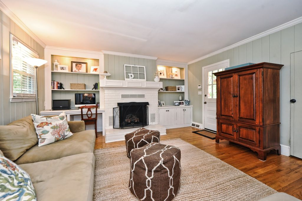 Cottage Living Room with Fireplace, Surya fallon ivory/dark chocolate pouf, double-hung window, Kascade wardrobe armoire