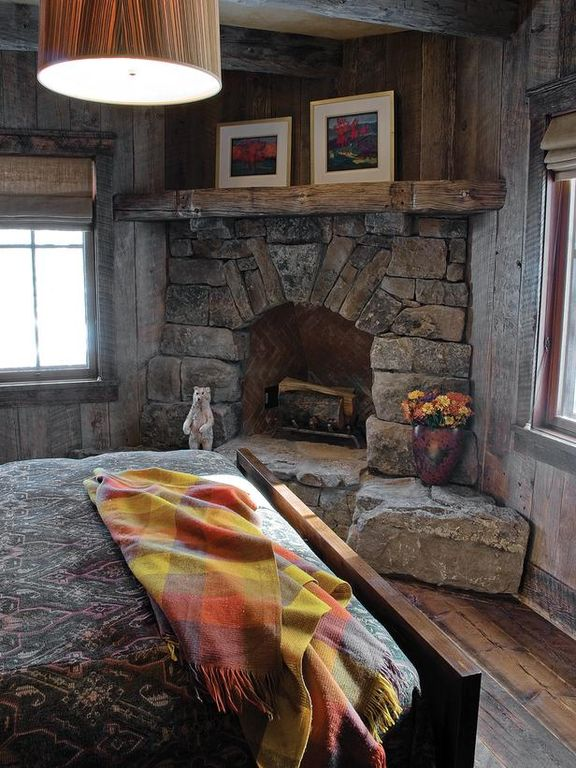 Rustic Guest Bedroom with Hardwood floors, Smith & noble flat roman fabric shades, stone fireplace, Pendant light