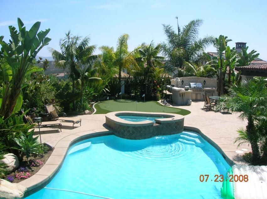 Tropical Swimming Pool with Outdoor kitchen, Pool with hot tub, exterior stone floors, Fence