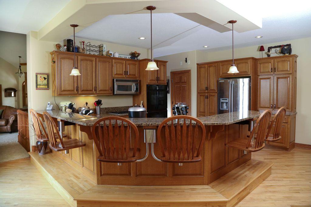 Country Kitchen with Pendant light, six panel door, Hardwood floors, flush light, double wall oven, Complex Granite, U-shaped