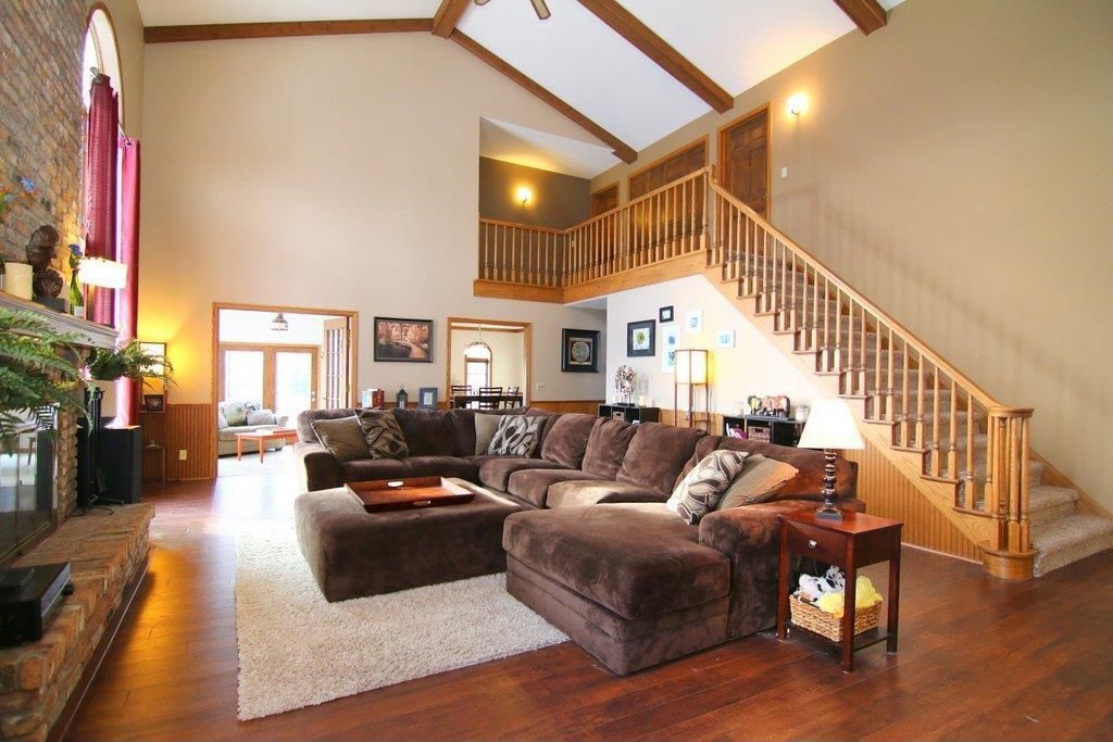 Craftsman Living Room with Paint 2, Paint 1, Hardwood floors, Signature design by ashley glenwood sectional, High ceiling