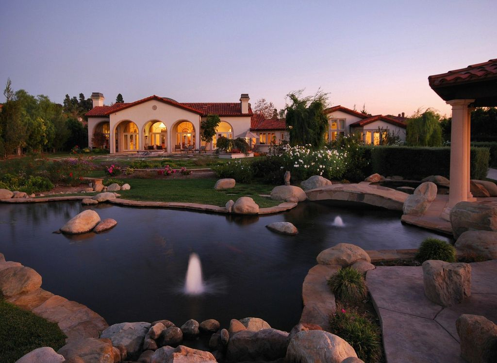 Mediterranean Exterior of Home with Natural rock pool accents, Arched window, Naturalistic pool, Casement, Gazebo