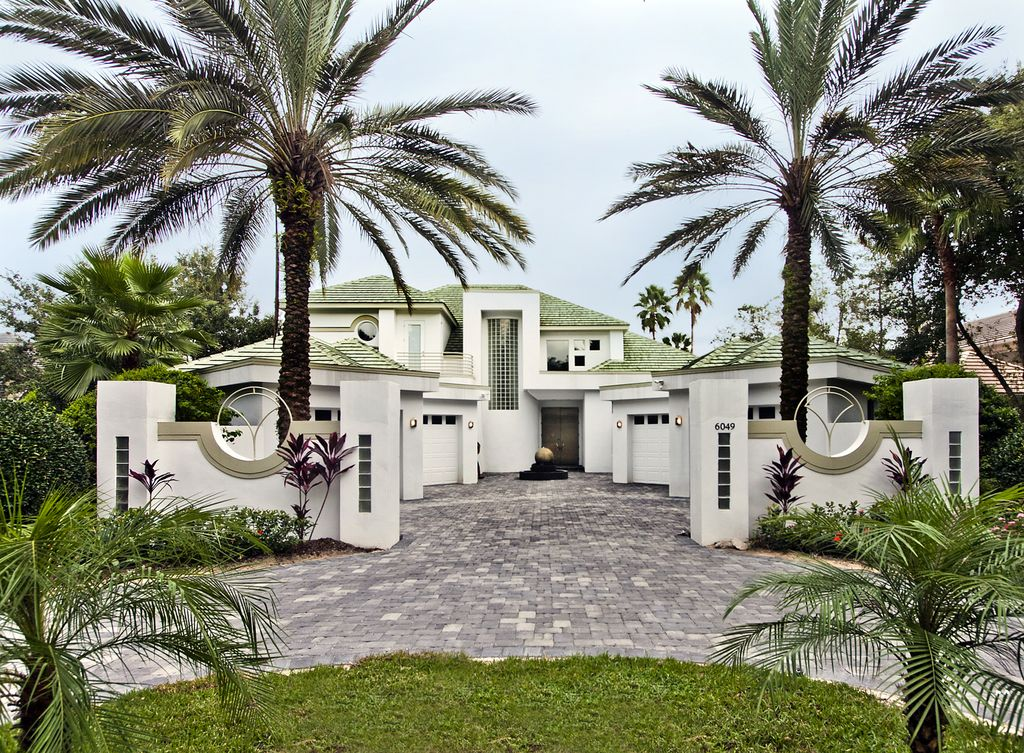 Tropical Exterior of Home with Brass sphere water fountain, Sphere water fountain, Palm trees, Paint, Cobblestone, Grass