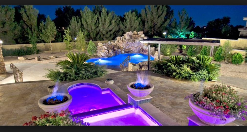 Tropical Swimming Pool with exterior stone floors, Fire pit, Fence, Trellis, Pool with hot tub