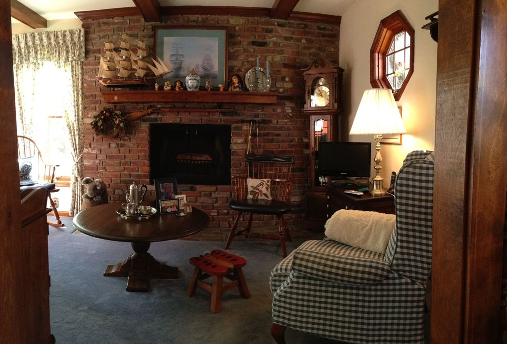 Country Living Room with Exposed beam, interior brick, Fireplace, Standard height, Carpet, specialty window, brick fireplace