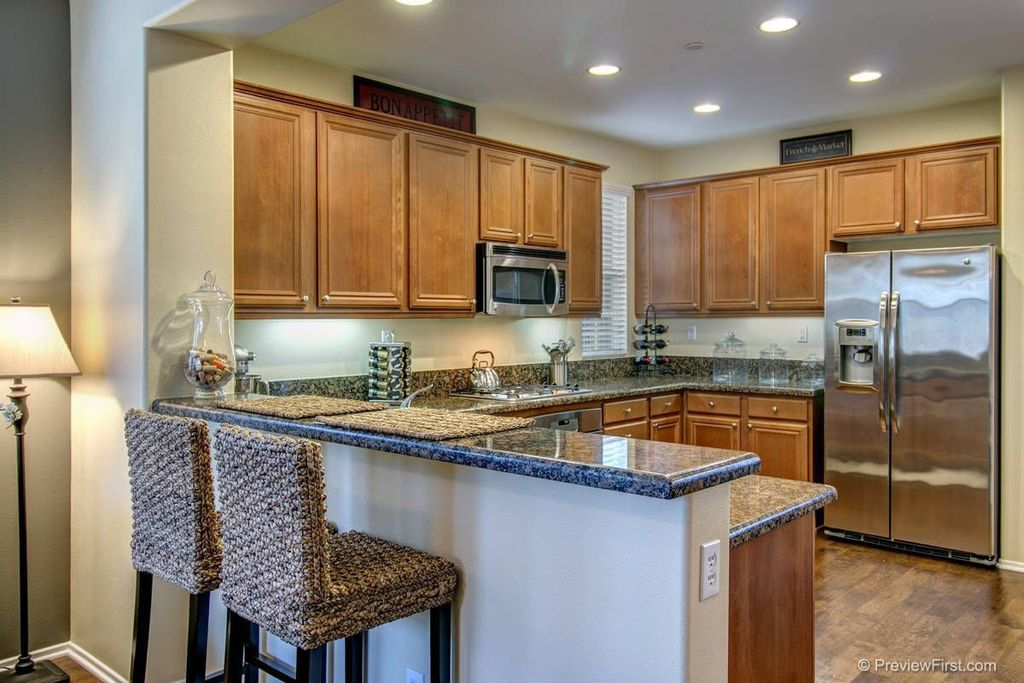 Craftsman Kitchen with U-shaped, Flat panel cabinets, can lights, Raised panel, built-in microwave, Complex granite counters