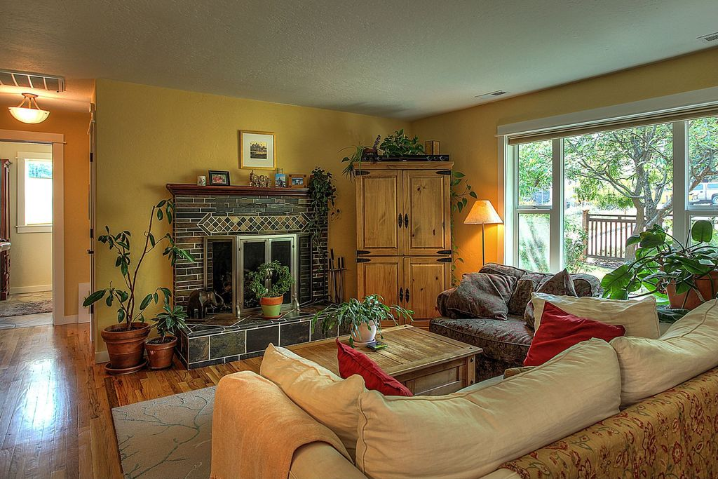 Traditional Living Room with stone fireplace, Hardwood floors, Area rug, Pine entertainment armoire