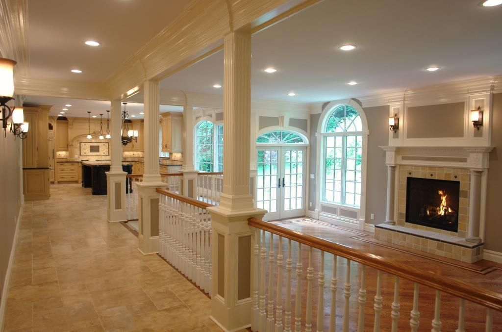 Traditional Great Room with stone fireplace, Wall sconce, sandstone tile floors, Arched window, Columns, can lights