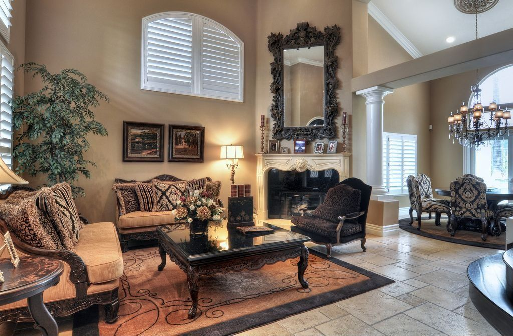 Traditional Living Room with limestone floors, Columns, Fireplace, High ceiling, Arched window, stone fireplace