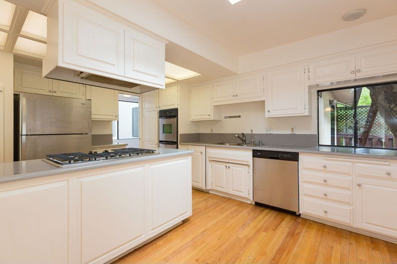 Traditional Kitchen with Casement, L-shaped, dishwasher, electric cooktop, Standard height, Hardwood floors, Skylight