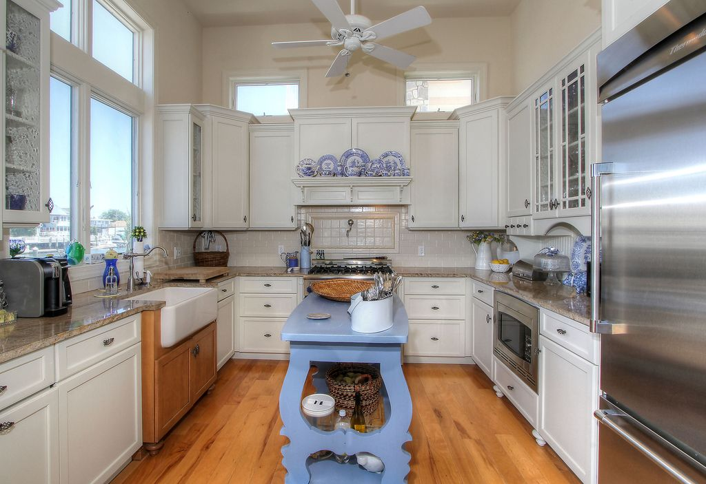 Cottage Kitchen with Custom hood, Ceiling fan, Flat panel cabinets, Glass panel, gas range, Multiple Refrigerators, Casement