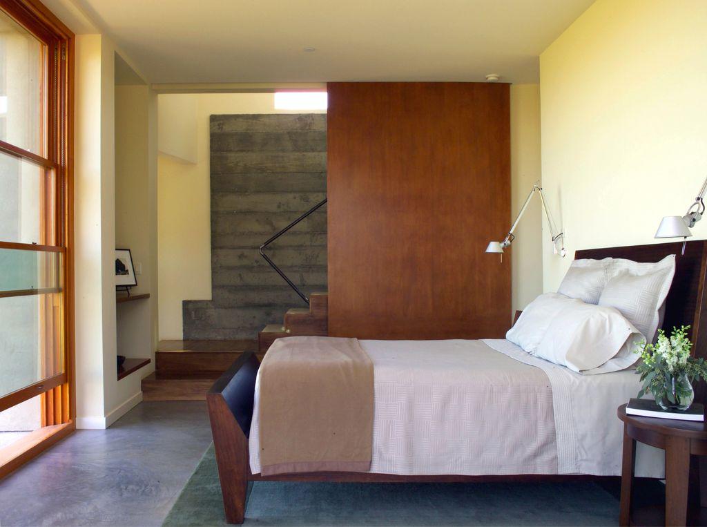 Modern Master Bedroom with sliding glass door, can lights, Built-in bookshelf, Concrete floors, Standard height