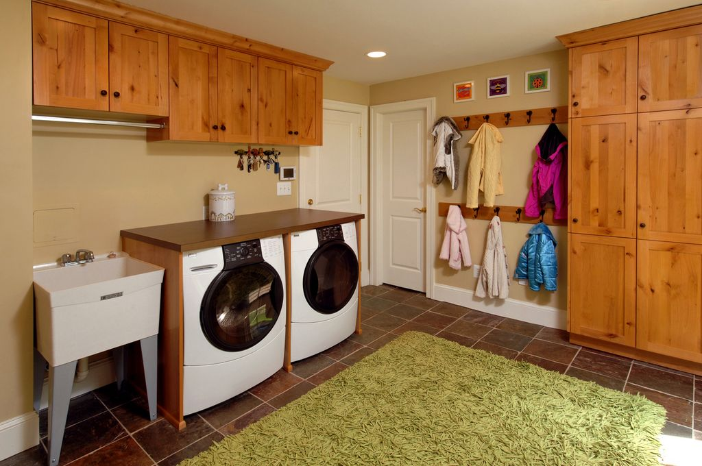 Country Laundry Room with Hanging Bar, stone tile floors, Farmhouse sink, Standard height, specialty door, laundry sink
