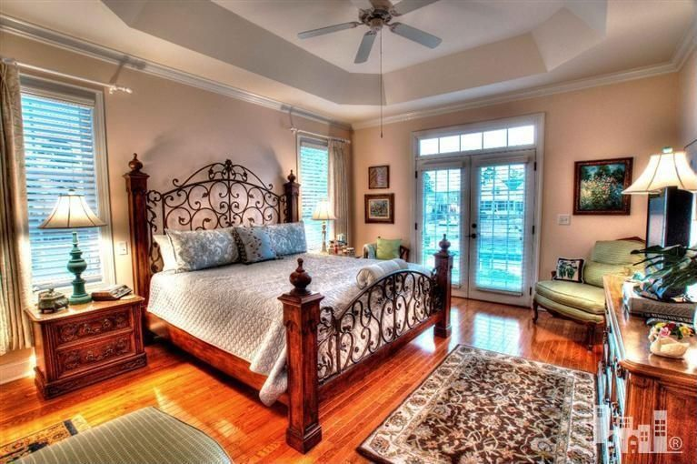 Mediterranean Master Bedroom with French doors, picture window, Standard height, Ceiling fan, Hardwood floors, Transom window