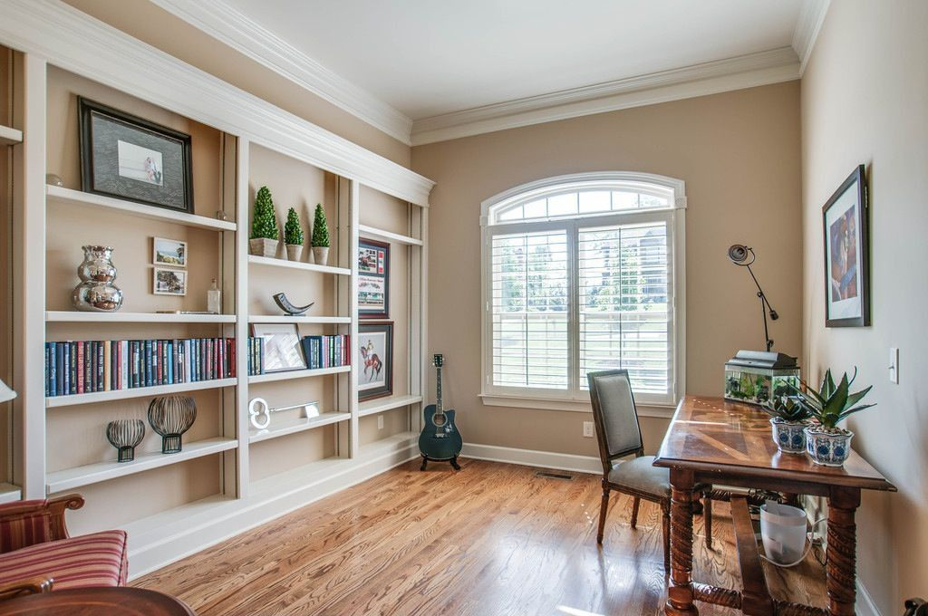 Traditional Home Office with Standard height, Arched window, Built-in bookshelf, Hardwood floors, Crown molding