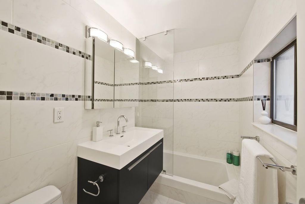 Contemporary Full Bathroom with Corian counters, drop in bathtub, Full Bath, European Cabinets, Towel warmer, Bathtub, Flush